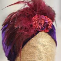 Turbante de terciopelo morado con detalle de plumas burgundy.