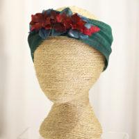 Turbante verde esmeralda con detalle de flores en rojo carmesí.